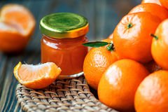 Homemade tangerine jam in glass jar with fruit around on a wooden table. Close-up, horizontal Stock Image