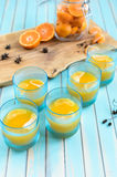 Homemade tangerine jelly in glasses over wooden rustic turquoise background Stock Photos