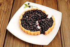Homemade tart with whole wild blueberries cut in square white pl Stock Photos