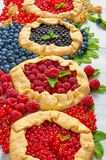 Homemade tarts with fresh blueberries, raspberries, red currants on the gray background. Vegetarian healthy berries galette. Homemade tarts with fresh Royalty Free Stock Images