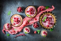 Homemade tarts with fresh raspberries and mascarpone. On old table stock image
