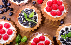 Homemade tarts with raspberries and blueberries on  wooden backg Royalty Free Stock Image