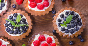 Homemade tarts with raspberries and blueberries on  wooden table Stock Photography