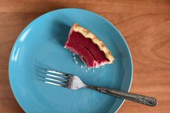 Homemade tasty berry pie half eaten on blue plate. Top view Royalty Free Stock Photo