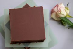 Homemade tasty brownie cake with dark chocolate cover. Stacked chocolate bars on plate chocolatey cacao gluten free natural delicious pastry creamy fudge rich royalty free stock image