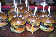 Homemade tasty grilled beef burger served for the guests party time. Delicious takeaway hamburgers waiting for guests . Shallow depth of fielsd. Shallow depth of Royalty Free Stock Images