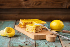 Homemade tasty layered lemon cake and whole and squeezed lemons. Closeup Royalty Free Stock Image