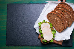 Homemade tasty sandwich with salad leaves and ham on a cutting board with cut slices of bread on a green wooden background Stock Photography