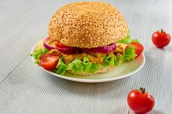 Homemade tasty vegetarian burger with salad, onion rings, cheese, cherry tomatoes and mustard on the gray background. Classic american veggie food. Close up Stock Photography