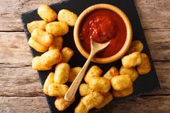 Homemade tater tots with tomato sauce close up. Horizontal top v. Homemade tater tots with tomato sauce close up on the table. Horizontal top view from above Royalty Free Stock Image