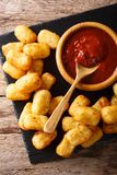 Homemade tater tots with tomato sauce close up. Vertical top vie. Homemade tater tots with tomato sauce close up on the table. Vertical top view from above Royalty Free Stock Photos