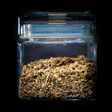Homemade tea leaves in glass container. Healthy homemade tea leaves in glass container isolated on black background Royalty Free Stock Images