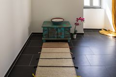 Homemade temple composed of a narrow rug and a small cabinet. To meditate royalty free stock images