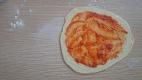 Homemade thin crust pizza with pizza sauce on top before bake Stock Photography