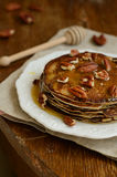Homemade thin pancakes with honey and pecan nuts on white porcel Royalty Free Stock Photo