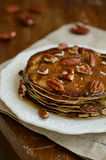 Homemade thin pancakes with honey and pecan nuts on white porcel Stock Photos