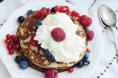 Homemade thin pancakes with whipped cream and fresh berries. Raspberry, black and red currant and bilberry Royalty Free Stock Photo