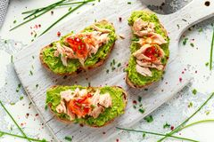 Homemade Toast sandwich with Salmon, Avocado and chilli jam on wihte wooden board. healthy food stock photos