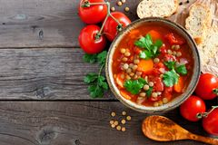 Homemade tomato, lentil soup, above view corner border on wood Royalty Free Stock Photo