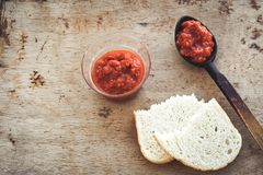 Homemade Tomato paste. Homemade  organic Tomato paste  and bread  an wooden spoon on wooden background Stock Images