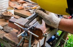 Homemade tool for repair. manufacture by own hands of the tool from iron. welding of metals. Close up photo of worker hand using sandpaper on metal workpiece Stock Image