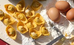 Homemade tortellini made with eggs and white flour. Background with homemade tortellini with eggs and white flour royalty free stock photos