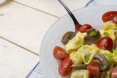 Homemade tortellini stuffed with mushrooms and spring onion and cherry tomatoes Stock Photography