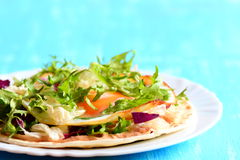 Homemade tortilla with fried egg, salad mix, hummus and parsley on a plate. Blue wooden background Stock Images