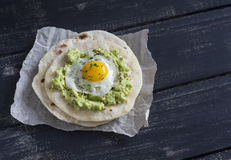 Homemade tortilla with mashed avocado and a fried quail egg. Royalty Free Stock Image