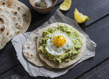 Homemade tortilla with mashed avocado and a fried quail egg. stock photography
