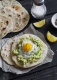 Homemade tortilla with mashed avocado and a fried quail egg. Stock Photos