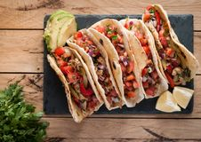 Homemade tortillas with spicy chicken, vegetables and salsa dip on wooden table, top view. Homemade tortillas with spicy chicken, avocado, mix of peppers, onion stock images