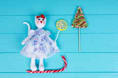 Homemade toy in the form of a cat in a dress on the candy sledge Stock Photos