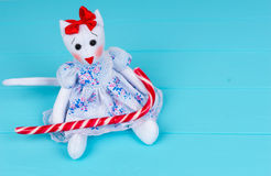 Homemade toy in the form of a cat in a dress holding candy cane Royalty Free Stock Images