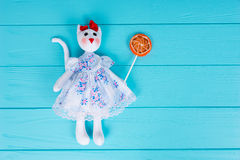 Homemade toy in the form of a cat in a dress holding colorful lo Royalty Free Stock Image