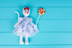 Homemade toy in the form of a cat in a dress holding colorful lo Royalty Free Stock Images