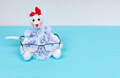 Homemade toy in the form of a cat in a dress holding stylish gla Royalty Free Stock Photography