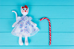 Homemade toy in the form of a cat in a dress lying near candy ca Royalty Free Stock Images