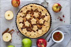 Homemade traditional American apple pie decorated with stars in a metal baking dish, apples, cinnamon sticks and a glass of tea. Royalty Free Stock Image