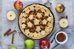 Homemade traditional American apple pie decorated with stars in a metal baking dish, red and green apples and cinnamon sticks. royalty free stock photo