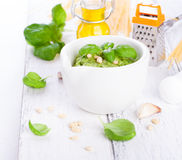 Homemade traditional basil pesto with olive oil, cedar nuts and garlic in a white bowl on a wooden rustic table Royalty Free Stock Photography