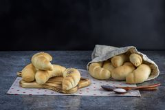 Homemade Traditional Czech pastry - white bread roll rohlik with salt and poppy seeds. On a wooden board stock images