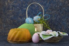 Easter bread and blue Easter eggs in a basket on dark stone table stock photography
