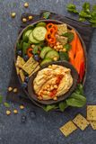 Homemade traditional hummus with vegetables, crackers on a black