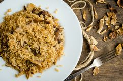 Homemade traditional Italian mushroom risotto. On wooden table. Classic Risotto with mushrooms and vegetables served on a white plate. Wild mushrooms risotto Stock Photo