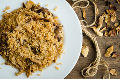 Homemade traditional Italian mushroom risotto. On wooden table. Classic Risotto with mushrooms and vegetables served on a white plate. Wild mushrooms risotto Royalty Free Stock Photography