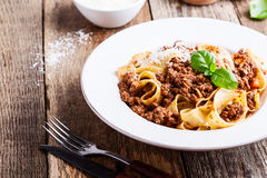 Homemade  traditional Italian pasta pappardelle bolognese. Served with Grana Padana cheese on rustic wooden table Stock Image