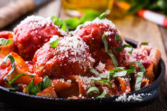 Homemade  traditional Italian pasta pappardelle with meatballs. And basil herb served with Grana Padana cheese in cast iron skillet on rustic wooden table Royalty Free Stock Photos