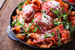 Homemade  traditional Italian pasta pappardelle with meatballs. And basil herb served with Grana Padana cheese on rustic wooden table Royalty Free Stock Image