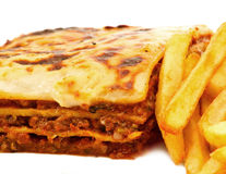 Homemade traditional lasagna and fries. A traditional lasagna made with minced beef bolognese sauce and three layers of pasta, lasagne in English Stock Photos